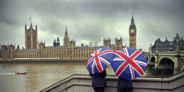 'Tourists huddle beneath British flag umbrellas (they sell them there) during a London summer rainstorm...