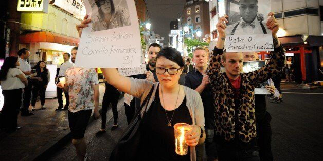 TOKYO, JAPAN - JUNE 14 : People pay tribute to victims of shooting at Pulse Nightclub in Orlando by holding...