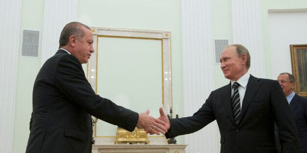 Russian President Vladimir Putin shakes hands with Turkey's President Recep Tayyip Erdogan, left, in...