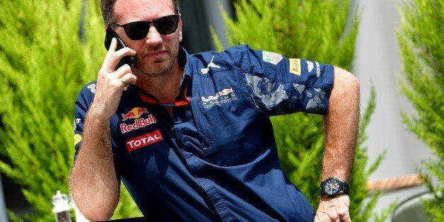 Infiniti Red Bull Racing's Team Chief Christian Horner speaks on his mobile phone in the paddock at the...