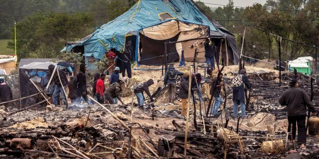 Migrants clean up burnt tents after a massive brawl that left 40 people injured in the 'Jungle' migrant...