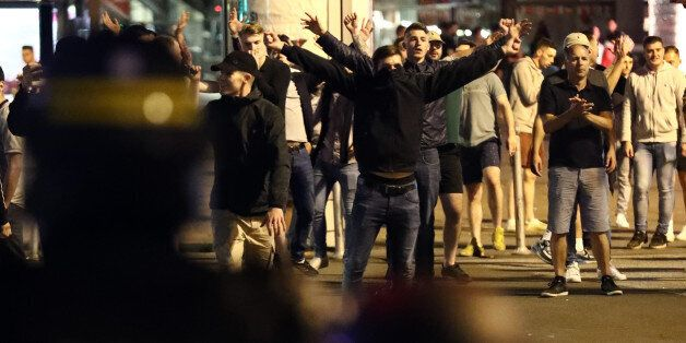 LILLE, FRANCE - JUNE 16: England fans gesture at police officers during clashes aon June 16, 2016 in...