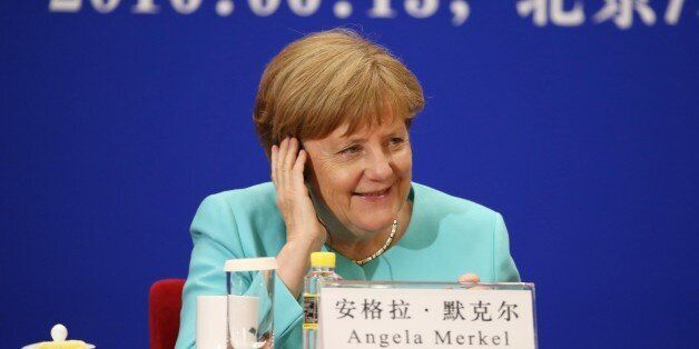 In this photo taken on June 13, 2016, German Chancellor Angela Merkel adjusts here headphones during...