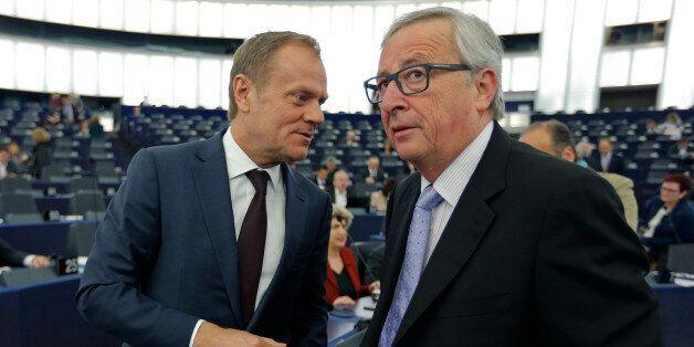 European Council President Donald Tusk (L) talks with European Commission President Jean-Claude Juncker...