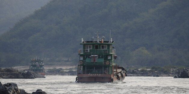 Chinese cargo ships sail on the Mekong river near the Golden Triangle at the border between Laos, Myanmar...