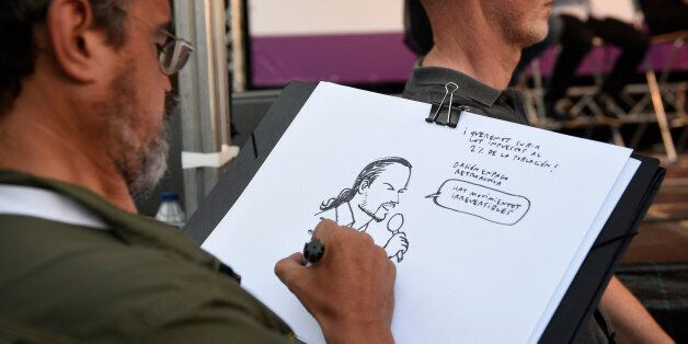 A man sketches a portrait of the leader of left wing party Podemos and party candidate for the upcoming...