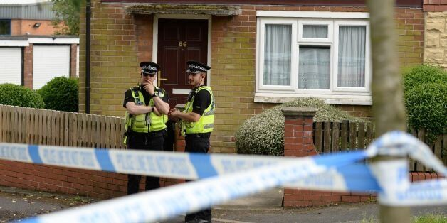 Police stand guard by a house suspected of being connected to the murder of Labour MP Jo Cox in Birstall,...