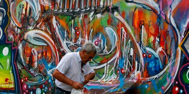 A man walks past a graffiti depicting the economic situation in Europe, in Lisbon August 22, 2011. Turbulent...
