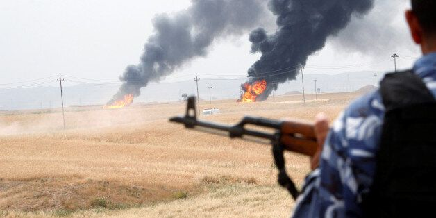 A member of the Kurdish security forces stands guard after explosions at two oil wells in Khabbaz oilfield,...