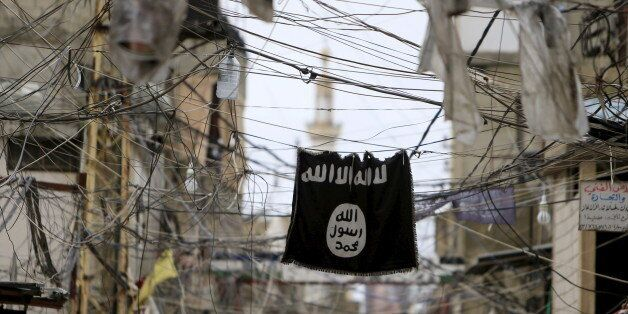 An Islamic State flag hangs amid electric wires over a street in Ain al-Hilweh Palestinian refugee camp,...