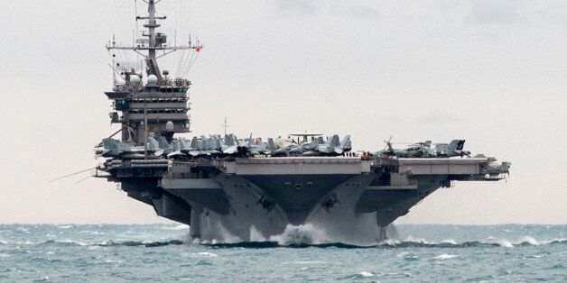 In this Saturday, Dec. 26, 2015 photo released by the U.S. Navy, the aircraft carrier USS Harry S. Truman...