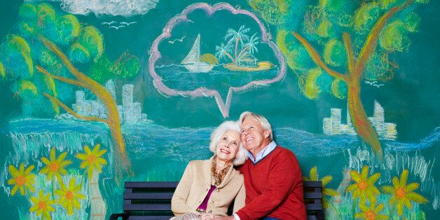 An elderly couple daydreaming on a park