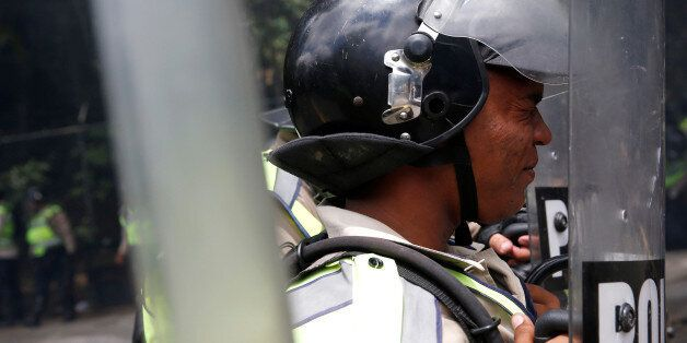 A riot police officer reacts to the tear gas effects as they clash with demonstrators during a protest...