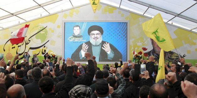 Lebanon's Hezbollah leader Sayyed Hassan Nasrallah addresses his supporters via a screen during a commemoration...