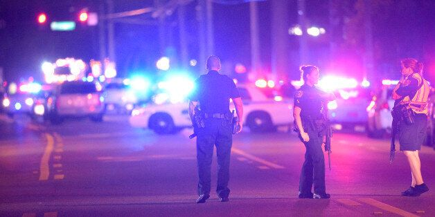Police officers stand guard down the street from the scene of a shooting involving multiple fatalities...
