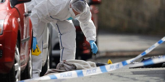 A forensics police officer works next women's shoes and a handbag on the ground behind a police cordon...