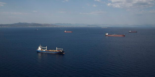 Oil tankers and container ships sit at their deepwater moorings in the Aegean sea off the coast of Athens,...
