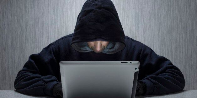 An anonymous hooded male using a tablet computer to represent a cyber criminal. (Photo by: Loop Images/UIG...