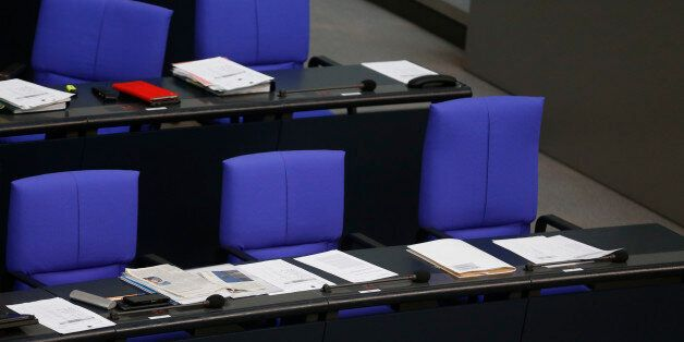 The chair (R) of German Chancellor Angela Merkel remains empty during a session of the Bundestag, lower...