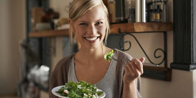 Portrait of an attractive young woman eating a salad in her kitchen