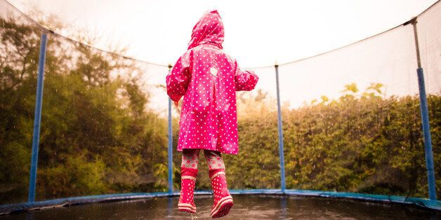 Little child wearing pink raincoat and boots jumping wet trampoline in