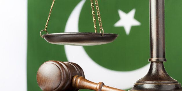 Gavel under the scale of justice. The national flag of Pakistan in the