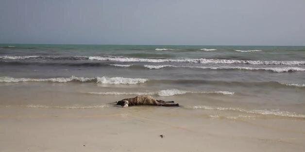 The lifeless body of a migrant lays on the beach near the western city of Zwara, Libya, Thursday June...