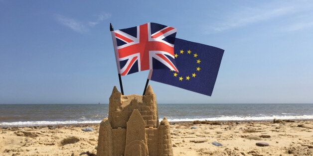 A sandcastle on a British beach with UK and European Union