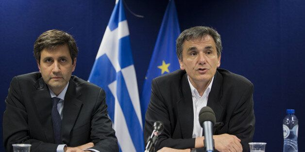 Euclid Tsakalotos, Greece's finance minister, right, speaks during a press conference after a Eurogroup...