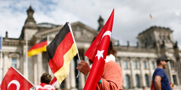 Demonstrators hold Turkish and German flags in front of the Reichstag, the seat of the lower house of...