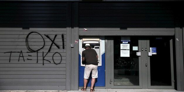 A tourist uses an ATM at a closed Attica Bank branch in Athens, Greece July 13, 2015. Euro zone leaders...