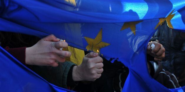 Demonstrators burn a European Union flag during a pro-migrant protest march in Kastanies on January 24,...