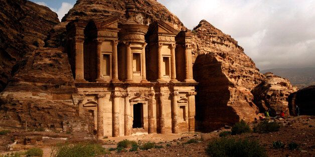 In this Feb. 23, 2016 photo, sun peaks out of rain clouds to light up the famous monastery in Petra southern...