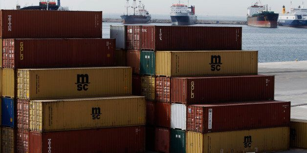 A man walks past containers at Piraeus port near Athens June 7, 2011. Greece will sell the 75 percent...
