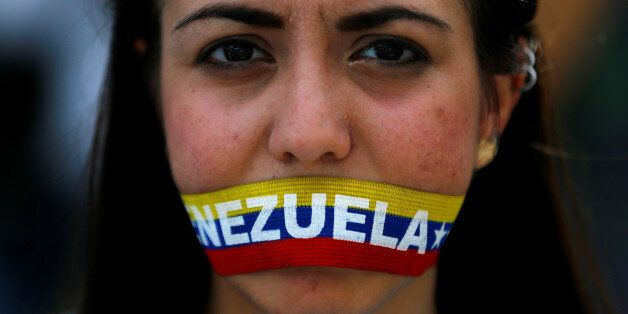 An opposition supporter covers her mouth during a rally to demand a referendum to remove President Nicolas...