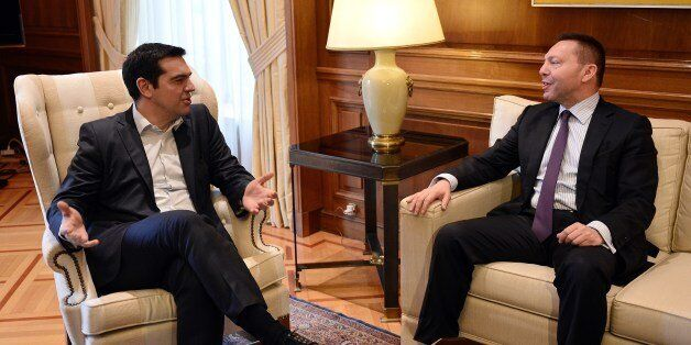 Greece's prime minister Alexis Tsipras (L) talks with the chairman of the Bank of Greece, Yiannis Stournaras...