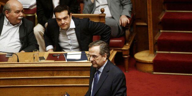 Antonis Samaras, Greece's former prime minister, front center, walks past Alexis Tsipras, Greece's prime...