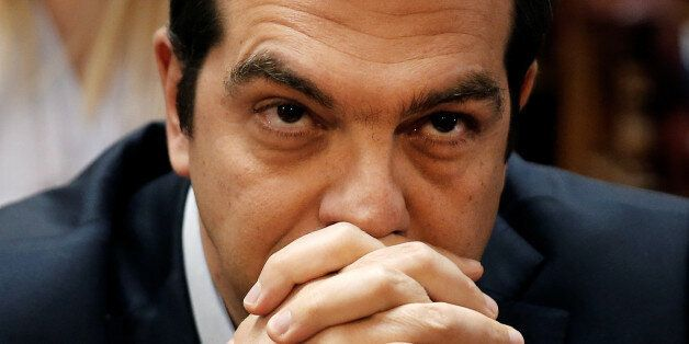 Greek Prime Minister Alexis Tsipras looks on before a ruling Syriza party parliamentary group session...