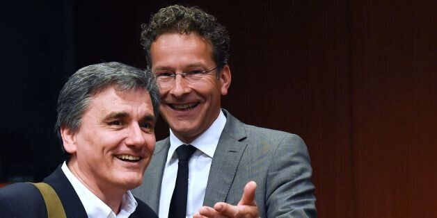 Greek Finance Minister Euclid Tsakalotos (L) talks with Dutch Finance Minister and president of the Eurogroup...