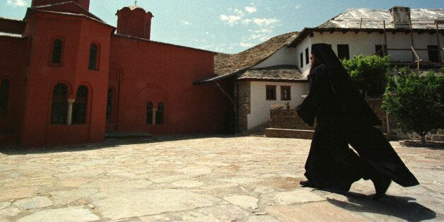 An Orthodox monk walks in courtyard of a monastery of autonomous community of Mount Athos in northern...