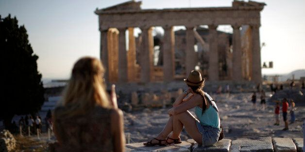 Tourists observe the Parthenon temple ruins on Acropolis Hill at sunset in Athens, Greece, on Monday,...