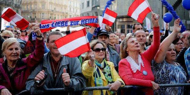 Austrian far right Freedom Party supporters wave flags during the final election rally in Vienna, Austria,...