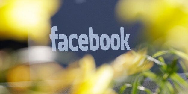 This Friday, May 18, 2012, file photo shows Facebook's headquarters behind flowers in Menlo Park, Calif....