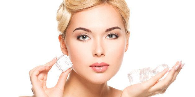 Beautiful young woman applies the ice to face. Skin care concept. Isolated on white.