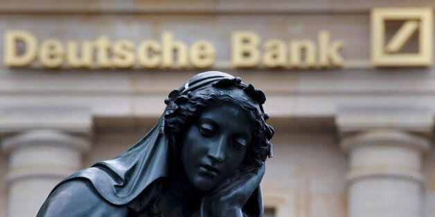 A statue is seen next to the logo of Germany's Deutsche Bank in Frankfurt, Germany, January 26, 2016....