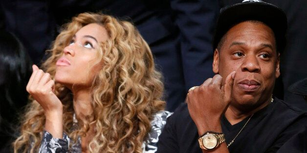 Singer Beyonce and her husband Jay-Z sit courtside before the NBA All-Star basketball game in Houston,...