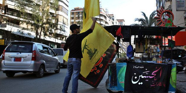 In this Feb. 29, 2016 photo, a vendor sells Hezbollah and religious flags and other memorabilia , in...
