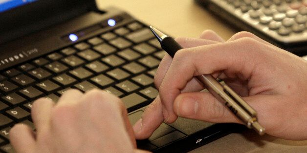 FILE - In this Feb. 1, 2012 file photo, a student works with a computer and a calculator at Reynoldsburg...