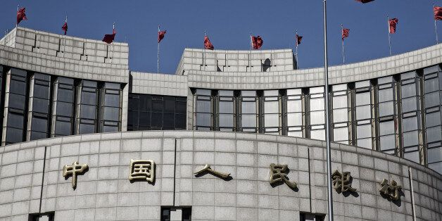A Chinese national flag flies above the People's Bank of China (PBOC) headquarters in Beijing, China,...