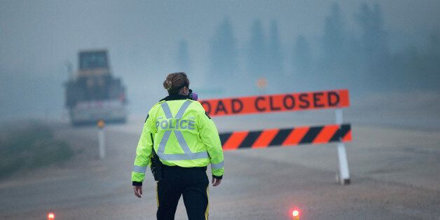 FORT MCMURRAY, AB - MAY 08: Smoke fills the air as a police officer stands guard at a roadblock along...